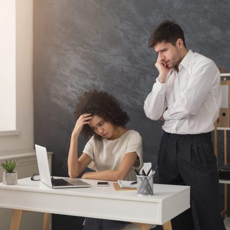 photo of worried man and woman looking at a laptop