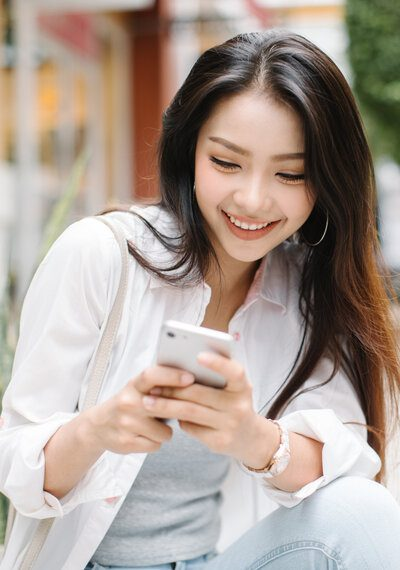 photo of happy woman texting on cell phone